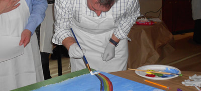 Man with apron paints a rainbow