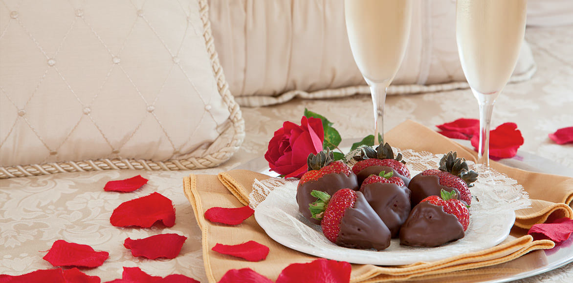 Chocolate-covered strawberries, two glasses of champagne, and red rose petals set out on a bed