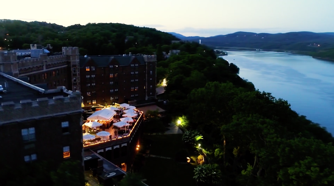 Drone photo of The Thayer Hotel and the Hudson River at dusk